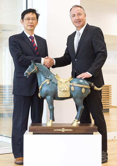 Lu Daming and, Vice-President and General Secretary of CMES and Oliver P. Kuhrt, CEO of Messe Essen shake hands after contract signing ceremony