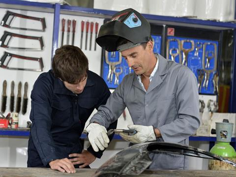 Trainee-with-instructor-using-welding-machine